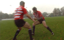 A rugby player dodges an opponent