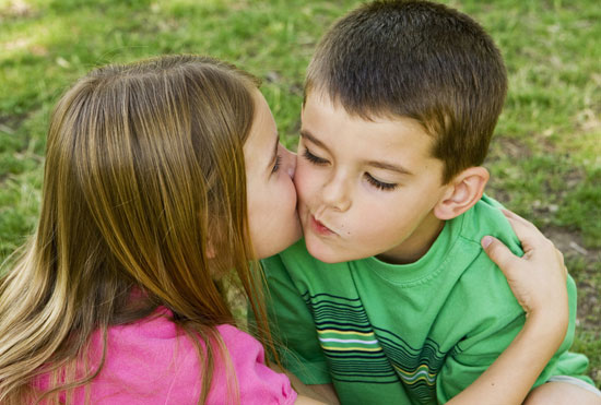 A girl and boy say hello with a kiss on the cheek © Phase4Photography Fotolia