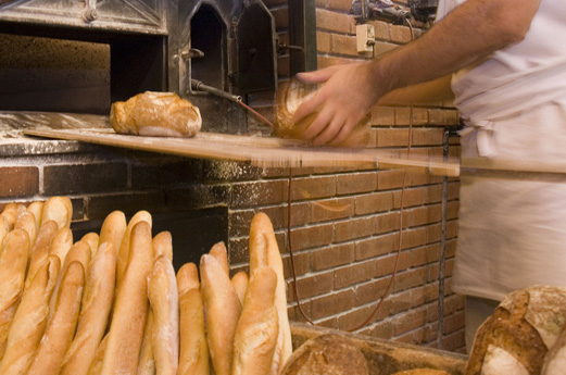 Baguettes and loaves of bread being taken out of a bread oven.