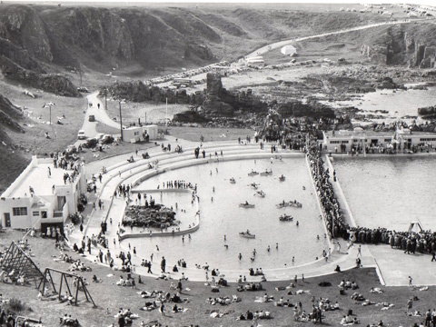 Black and white view, looking down from coastal cliffs to twin open air pools, with an Art Deco pavilion to the left of frame. One pool contains a mix of people paddling and rowing boats. The pool to the right is surrounded by a crowd of people, possibly watching a swimming competition. A large number of people are sunbathing on the surrounding grassy area.