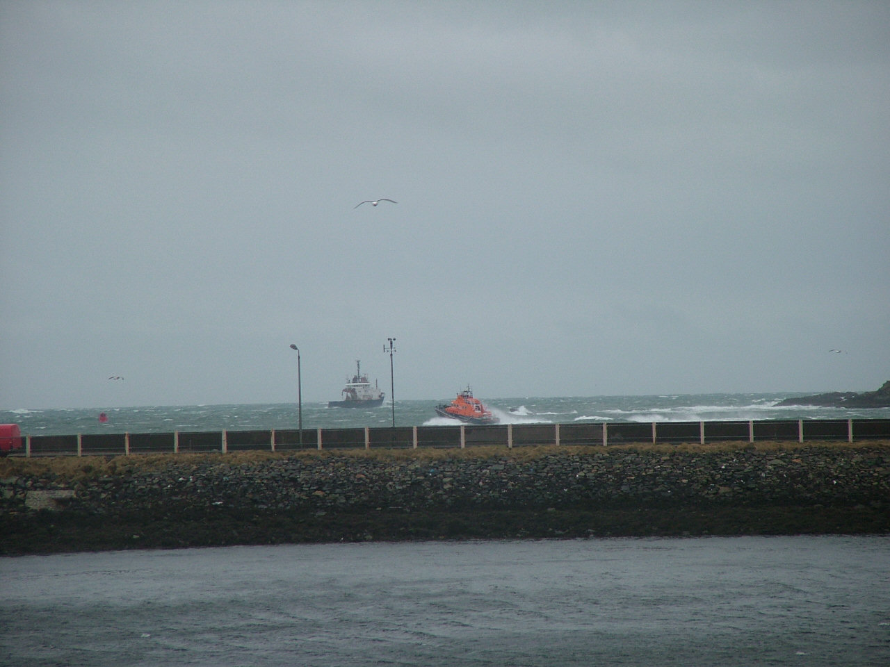 Lifeboat going out; tugboat heading in same direction