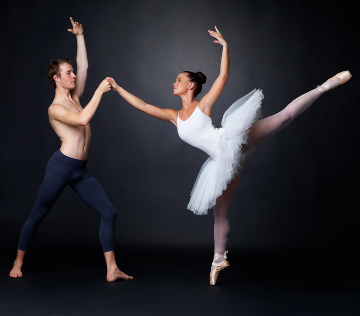 Two graceful ballet dancers performing against black background @ Yuri Arcurs - fotolia.com