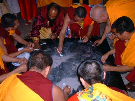 All the monks help to scoop up the coloured sand, now swept into heaps of nondescript grey, using white plastic teaspoons