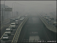 Vehicles drive on a street which is shrouded with smog on July 8, 2008 in Beijing.