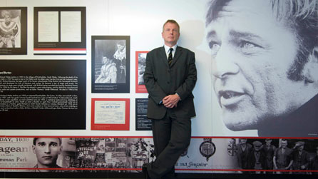 Professor Chris Williams in front of a display of Richard Burton pictures and documents. Photo courtesy of Swansea University.