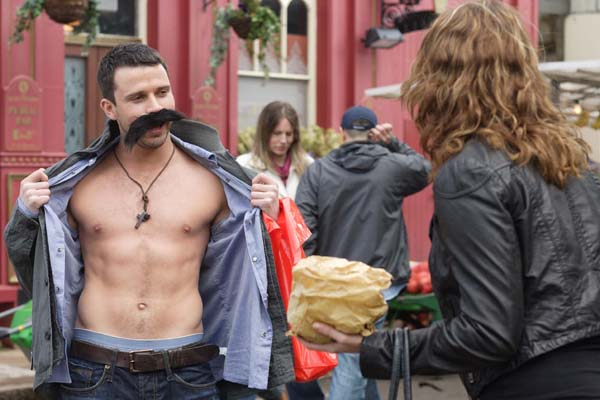 EastEnders' Ryan Malloy, played by Neil McDermott, unbuttons his shirt to reveal his torso to Janine Butcher, played by Charlie Brooks, in the middle of Albert Square. EastEnders will be broadcast in HD by the end of the year