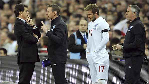 Fabio Capello chats with Stuart Pearce while David Beckham prepares to appear