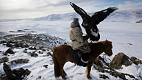 A Kazakh hunter with the golden eagle he has trained to hunt foxes