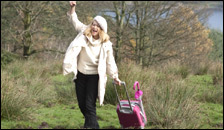 A woman pulling a pink suitcase through a field