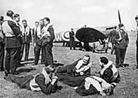 Black and white photograph showing a group of RAF pilots by a plane