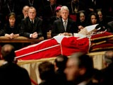 Body of John Paul II on display in Rome, with former American presidents George HW Bush and Bill Clinton in background