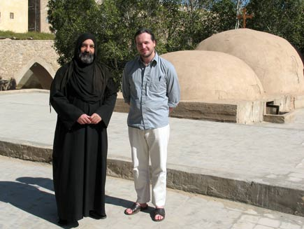 Father Iranaeus, dressed head to foot in black monastic robes with a scarf covering his head, with Nicholas Buxton in a stone courtyard inside the Monastery of Saint Macarius, with two domed roofs behind and below them