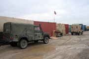 Army vehicles next to containers and tents on a British military base in Iraq