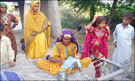 An old lady in Sindh province, Dhaanani, holds her sickly great grandson - her daughter and her granddaughter both died in childbirth