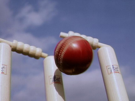 A cricket ball hitting stumps