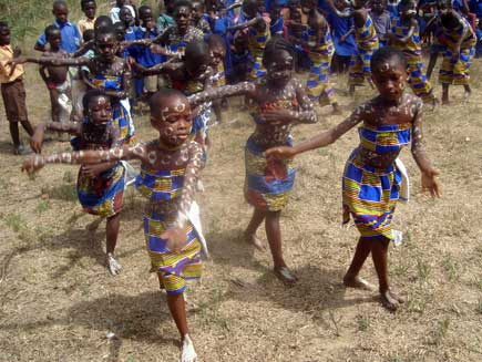 Schoolchildren dancing in colourful outfits and body paint