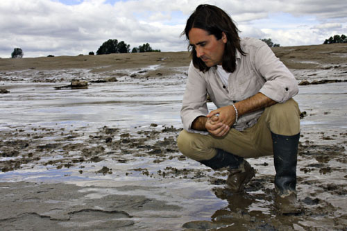 Neil Oliver looking at footprints in the mud in Newport