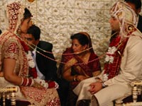 Bride and groom with string tied around both of them as they face each other