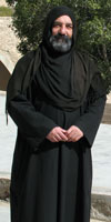 Father Irenaeus, Coptic monk in full black robe and headscarf with short beard