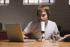 a man recording a podcast with a microphone and computer.