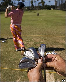 John Daly's caddy shows off some of the 20-year-old wedges while the player practises on the driving range