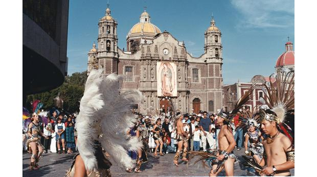 Mexican dancers dressed in Aztec-style clothing outside the shrine of the Virgin of Guadalupe, Mexico City. Getty Images