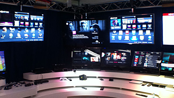 Bank of TVs and monitors over an arena in which remote controls site, watching.