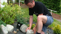 man putting rocks in a garden