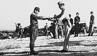 A Japanese army captain surrenders his sword to an American officer on Saipan