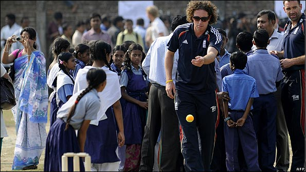 Ryan Sidebottom throws a ball to a girl during the visit to the school. (Pic: AFP)