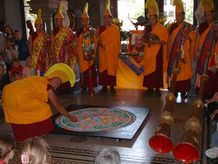 The monks are in full ceremonial dress now, wearing orange robes over their red tunics and orange and yellow crested headdresses. Tall Tibetan horn instruments are also visible.  One monk has begun destroying the mandala by scraping his knuckle in a radial direction through the sand