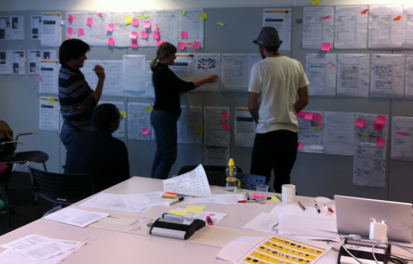 A meeting, poring over designs on the wall