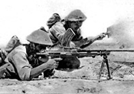 Photograph showing two British troops lying on the ground aiming machine guns (1942)