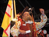 Wimborne Town Crier Chris Brown, waving the St Wite's Cross at Camp Bestival in July 2008
