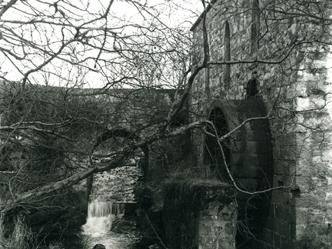 Black and white view of a watermill and wheel next to a narrow burn. An arched stone bridge crosses the burn over a small weir or waterfall.