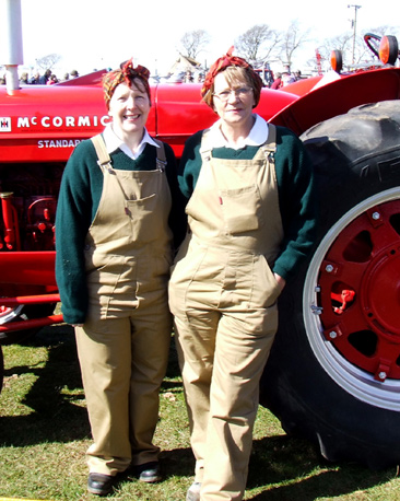 Two women lean on tractors dressed as the womans land army