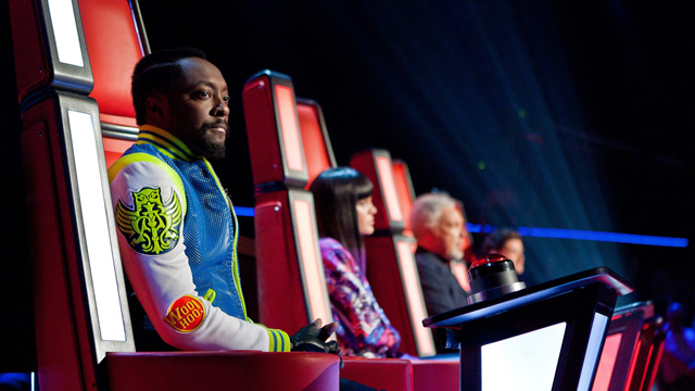 The Voice judges sit in their red chairs.