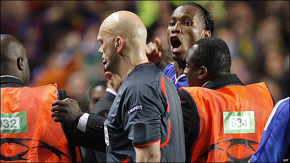 Drogba has to be restrained by stewards from confronting the referee