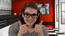 teenage girl with glasses making a thumbs up gesture