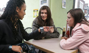 Model Scout Marcella (Angela Murray) hands Ashley (Sinead Moynihan) a business card much to the surprise of Ashley's sister Jade (Linzey Cocker)