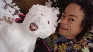 Liz Carr smiling next to her toothy snowman