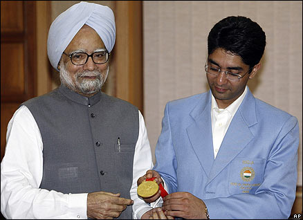 Indian shooter Abhinav Bindra shows his Olympic gold medal, to Indian Prime Minister Manmohan Singh