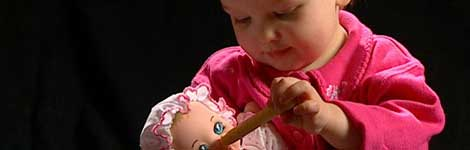 Child plays with doll