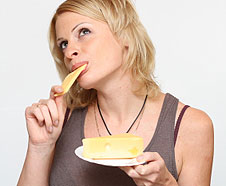 A young woman eating a plate of cheese.