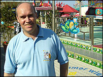 BBC Radio Manchester reporter Ian Cheeseman in front of a funfair ride in Hamburg
