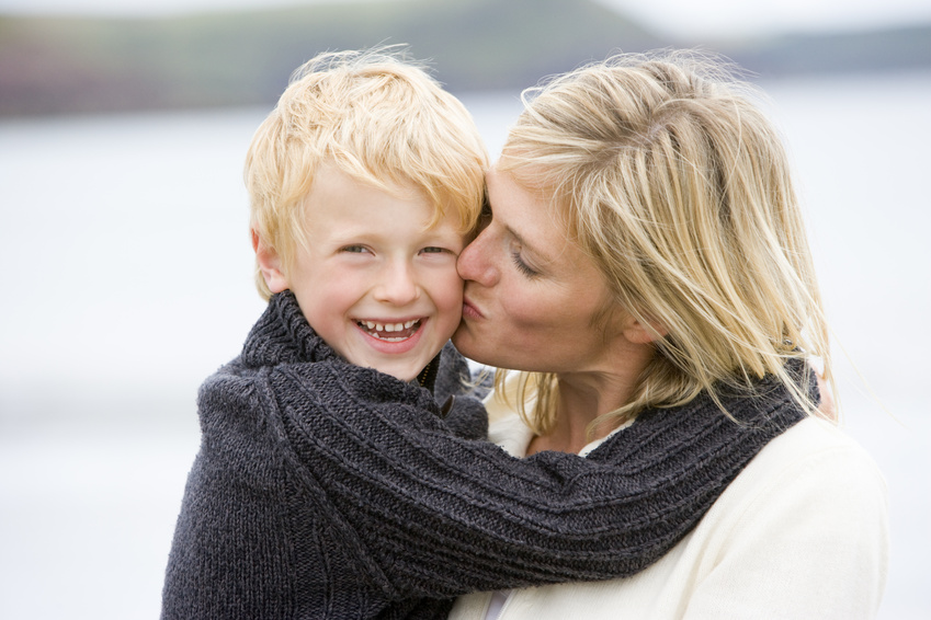 Mother kissing son at beach smiling @ monkey business - fotolia