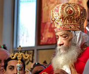 The Coptic Orthodox Pope Shenouda III, bearded gentleman in red and gold robe, with head bowed as if in prayer