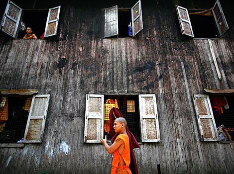 A Buddhist monk carries his robe as another looks out of the window of their monastery.