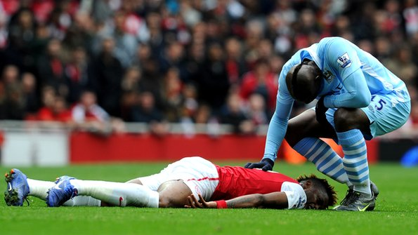 Mario Balotelli reaches towards the injured Bacary Sagna