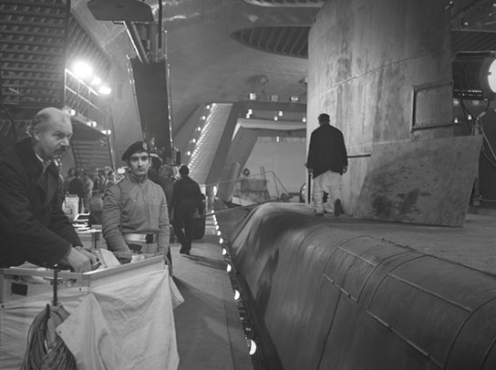 Crew and extras mingle on the quayside next to the hull of a prop submarine.